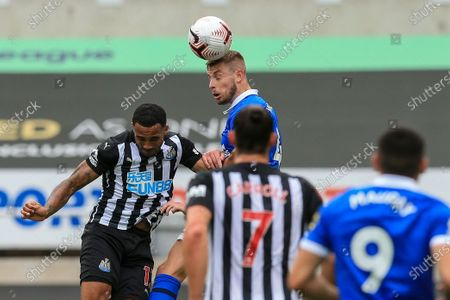 Adam Webster (4) of Brighton and Hove Albion in an aerial challenge Callum Wilson (13) of Newcastle United