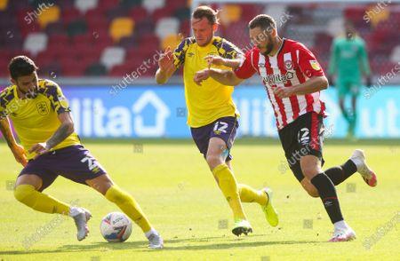 Henrik Dalsgaard of Brentford is obstructed by Richard Stearman of Huddersfield Town (12)