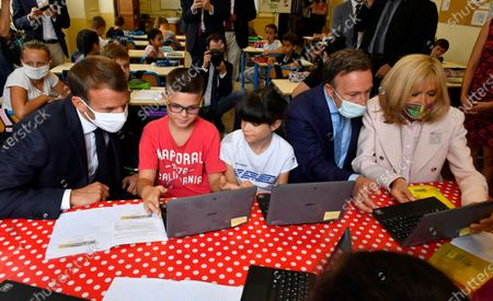 French President Emmanuel Macron, left, his wife Brigitte Macron, right, and cultural special adviser Stephane Bern wearing protective face masks against the conoravirus visit a school at the eve of the heritage day in Condom, southwestern France