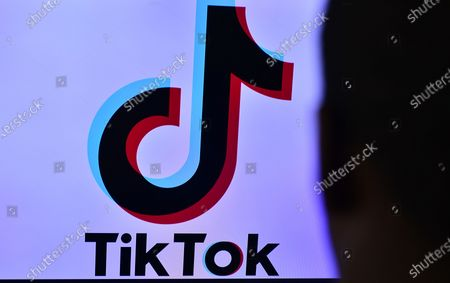 This photo illustration taken on September 18, 2020 shows the logo of the social network application TikTok (front) as boy stand in front of the screens in Miami, Florida.