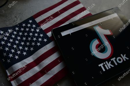 This photo illustration taken on September 18, 2020 shows the logo of the social network application TikTok (top) and a US flag (bottom) shown on the screens of a ipad in Miami, Florida.