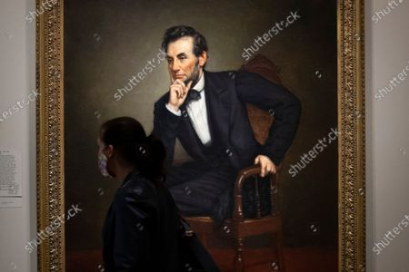 Stock Photo of A person walks by a portrait of the sixteenth US President, Abraham Lincoln, by artist George Peter Alexander Healy; in the exhibit 'America's Presidents' at the National Portrait Gallery, in Washington, DC, USA, 18 September 2020. The Smithsonian reopened four additional museums on 18 September, that were closed since mid-March as a public health precaution amidst the coronavirus COVID-19 pandemic. The four museums reopened are the National Museum of African American History and Culture, the Renwick Gallery, the National Portrait Gallery and the Smithsonian American Art Museum.