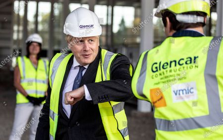 Britain's Prime Minister Boris Johnson bumps elbows with scientists as he visits the construction site of the new vaccines Manufacturing and Innovation Centre (VMIC), currently under construction on the Harwell science and innovations campus near Didcot, England