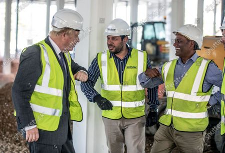 Britain's Prime Minister Boris Johnson bumps elbows with construction workers as he visits the construction site of the new vaccines Manufacturing and Innovation Centre (VMIC), currently under construction on the Harwell science and innovations campus near Didcot, England