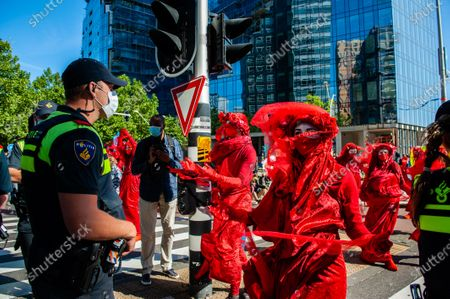 The Red Rebels seen performing in front of the police during the demonstration. Preview to the blockade, climate activists gathered at the Gustav Mahlerplein during a legal demonstration, where the Red Rebels showed up. After that, the activists blocked the main road of the financial district during an act of peaceful civil disobedience. With these actions, XR demands a Citizen's Assembly for fair climate policy. After a few hours, several of them were arrested by the Dutch police.