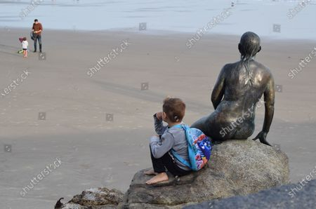 Stock Image of The Kent seaside town of Folkestone, early evening. Image shows The Folkestone Mermaid by Cornelia Parker, forever gazing out to sea, across Sunny Sands beach.