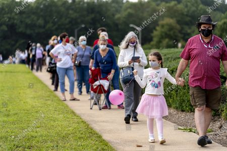 Steven Daftarian of Fairfax, Va., and his daughter Laleh, 6, wait in a line stretching the equivalent of two football fields as hundreds wait in line for early voting at Fairfax County Government Center, in Fairfax, Va