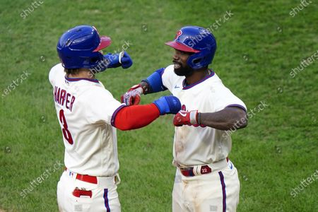 Philadelphia Phillies' Bryce Harper, left, and Andrew McCutchen celebrate after Harper's two-run home run off Toronto Blue Jays pitcher Robbie Ray during the fifth inning of the first baseball game in a doubleheader, in Philadelphia