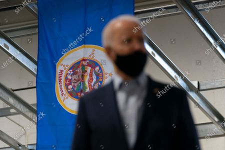 Stock Photo of Minnesota state flag hang above Democratic presidential candidate former Vice President Joe Biden as he tours Jerry Alander Carpenter Training Center in Hermantown, Minn