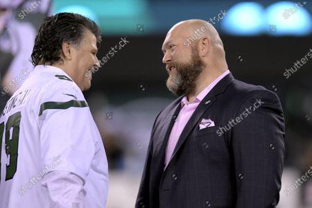 Former New York Jets defensive end Mark Gastineau, left, speaks with Jets general manager Joe Douglas during halftime of an NFL football game, in East Rutherford, N.J