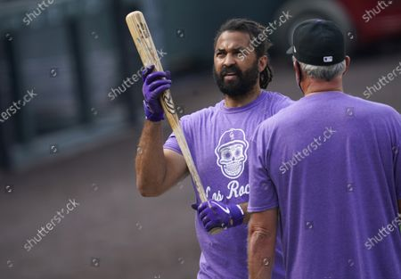 Colorado Rockies left fielder Matt Kemp, left, confers with batting coach Dave Magadan as Kemp warms up before a baseball game against the Los Angeles Dodgers, in Denver