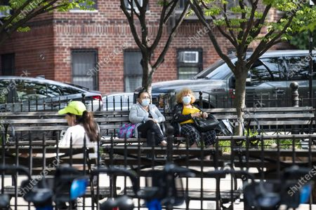 Two women wearing PPE masks sit on a park bench at Father Demo Square on Bleeker Street in The West Village in Manhattan, New York. Mandatory credit: Kostas Lymperopoulos/CSM