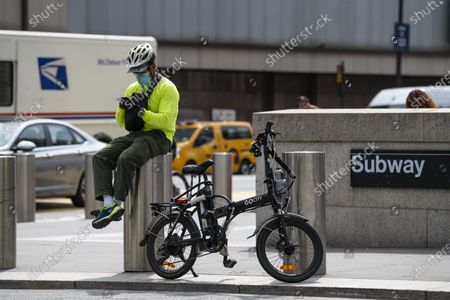 A man wearing PPE sits and looks at his cell phone along 8th Avenue with his Gocity bike in Manhattan, New York. Mandatory credit: Kostas Lymperopoulos/CSM