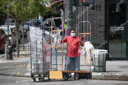 A man wearing PPE prepares to cross the street and receive a product delivery in Manhattan, New York. Mandatory credit: Kostas Lymperopoulos/CSM