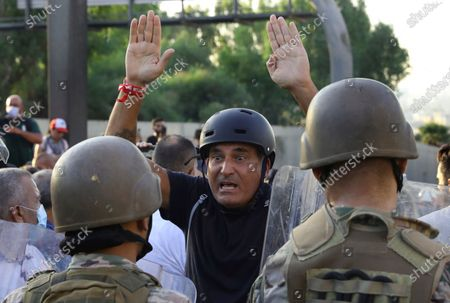 Stock Image of An anti-government protester reacts in front of Lebanese soldiers during a protest against President Michel Aoun near the presidential palace in Baabda, east of Beirut, Lebanon, on . Soldiers fired rubber bullets and live rounds in the air to disperse hundreds of protesters trying to march to the presidential palace