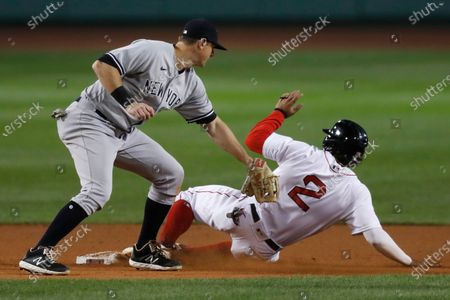 New York Yankees' DJ LeMahieu puts on a late tag as Boston Red Sox's Xander Bogaerts (2) advances to second base on a wild pitch by Jordan Montgomery during the fifth inning of a baseball game, in Boston