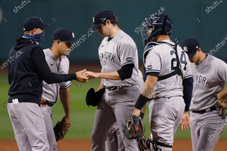 New York Yankees manager Aaron Boone, left, removes Jordan Montgomery, center, during the fifth inning of the team's baseball game against the Boston Red Sox, in Boston