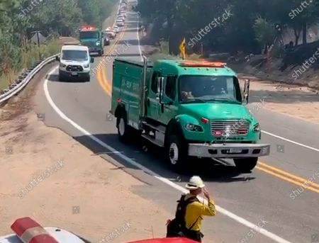 This image taken from video and provided by the Orange County Fire Authority shows a firefighter saluting as a procession carrying a fallen firefighter passes by at the El Dorado Fire in Southern California, . The death of a firefighter on the lines of a wildfire east of Los Angeles was under investigation Friday as another blaze to the north threatened small communities on the edge of the Mojave Desert