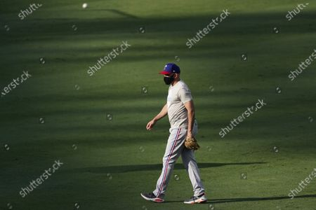 Texas Rangers manager Chris Woodward walks on the field during batting practice before the team's baseball game against the Los Angeles Angels, in Anaheim, Calif