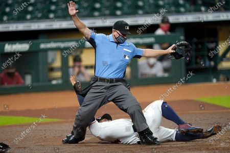 Stock Image of Houston Astros' George Springer, bottom, rolls into home plate umpire Mike Muchlinski after scoring on a wild pitch by Arizona Diamondbacks starting pitcher Zac Gallen during the first inning of a baseball game, in Houston
