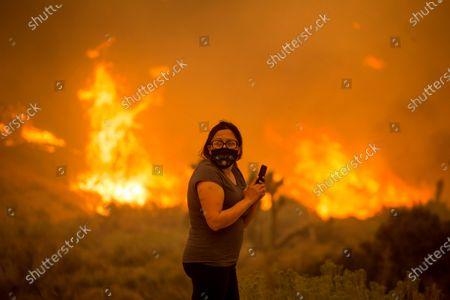 Woman watches as the Bobcat Fire burns in Juniper Hill, Calif