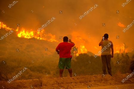 People take photos as the Bobcat Fire burns in Juniper Hill, Calif