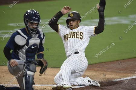 San Diego Padres' Trent Grisham, right, slides as he scores past Seattle Mariners catcher Luis Torrens, left, during the third inning of a baseball game, in San Diego. Grisham scored on wild pitch