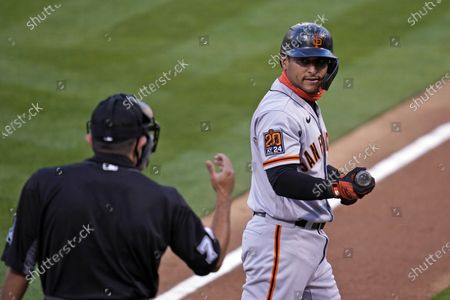 San Francisco Giants' Donovan Solano, right, looks at home plate umpire Alfonso Marquez and walks back to the dugout after striking out swinging against Oakland Athletics starting pitcher Chris Bassitt in the first inning of a baseball game, in Oakland, Calif