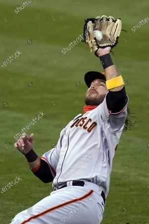 Stock Photo of San Francisco Giants shortstop Brandon Crawford catches a foul ball hit by Oakland Athletics' Tommy La Stella in the first inning of a baseball game, in Oakland, Calif