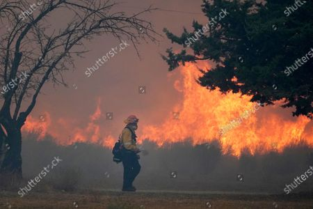Capt. Dan Engkraf of Los Angeles County Fire stands walks along the driveway of a home along Cima Mesa Rd. as crews protect structures from the advancing Bobcat fire, in Juniper Hills, Calif