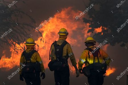 Members of a Los Angeles County Fire crew make a stand to protect a home from the advancing Bobcat Fire along Cima Mesa Rd., in Juniper Hills, Calif