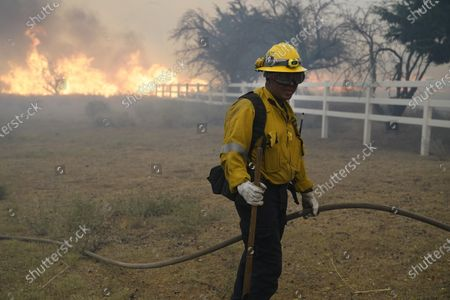 Stock Photo of Robert Ortiz of Los Angeles County Fire holds a water hose while protecting a home from the advancing Bobcat fire along Cima Mesa Rd., in Juniper Hills, Calif