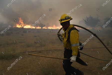 Robert Ortiz of Los Angeles County Fire holds a water hose while protecting a home from the advancing Bobcat Fire along Cima Mesa Rd., in Juniper Hills, Calif
