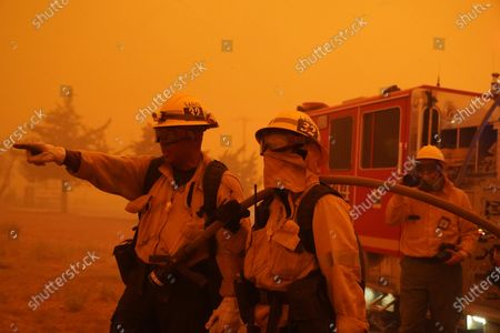 Robert Ortiz, left, and Alexis Miller of Los Angeles County Fire talk about a plan of attach while protecting a home from the advancing Bobcat Fire along Cima Mesa Rd., in Juniper Hills, Calif