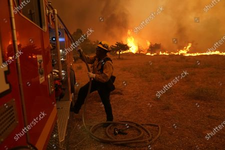 Stock Image of Robert Ortiz of Los Angeles County Fire works around a fire engine while protecting a home from the advancing Bobcat Fire along Cima Mesa Rd., in Juniper Hills, Calif