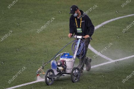 Stock Image of Field worker sprays a solvent to remove paint marking the goal box on the turf at CenturyLink Field following an MLS soccer match between the Seattle Sounders and Los Angeles FC, in Seattle. The stadium is being prepared Sunday's NFL football game between the Seattle Seahawks and the New England Patriots