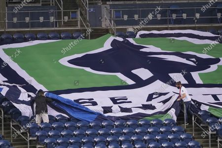 Workers remove a Seattle Sounders banner from the stands at CenturyLink Field following an MLS soccer match between the Sounders and Los Angeles FC, in Seattle. The stadium is being prepared for Sunday's NFL football game between the Seattle Seahawks and the New England Patriots