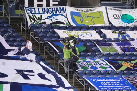 Workers remove banners supporting the Seattle Sounders from the stands at CenturyLink Field following an MLS soccer match between the Sounders and Los Angeles FC, in Seattle. The stadium is being prepared for Sunday's NFL football game between the Seattle Seahawks and the New England Patriots