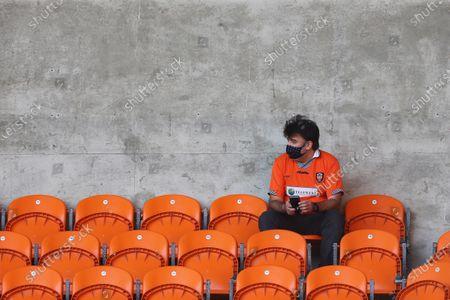 A mask wearing Blackpool fan sits alone