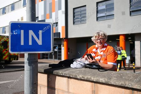 A Blackpool fan waits to enter the stadium