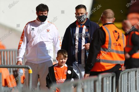 Blackpool fans in masks make their way to their seats past stewards
