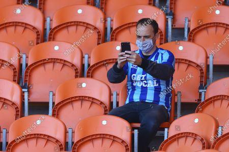 A mask wearing Blackpool fan takes a selfie