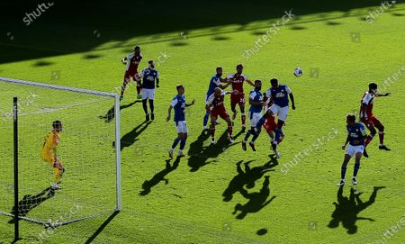 Players cast shadows on the pitch while they jump to a corner ball / Editor's Picks