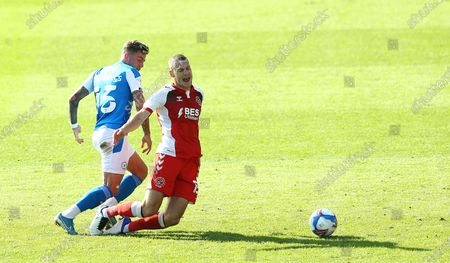 Paul Coutts of Fleetwood Town is fouled by Sammie Szmodics of Peterborough United
