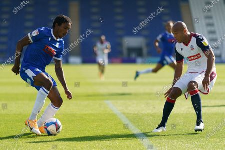 Jevani Brown of Colchester United runs with the ball towards Alex Baptiste of Bolton Wanderers