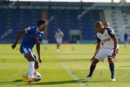 Jevani Brown of Colchester United runs at Alex Baptiste of Bolton Wanderers
