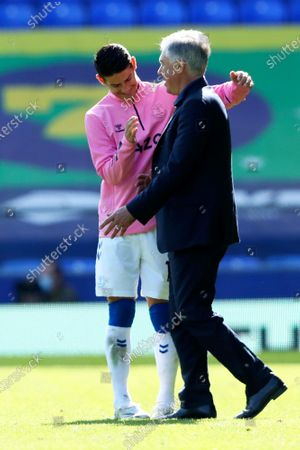 Everton's James Rodriguez, left, celebrates with Everton's manager Carlo Ancelotti at the end of the English Premier League soccer match between Everton and West Bromwich Albion at Goodison Park in Liverpool, England . Everton won 5-2