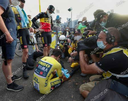 Slovenia's Primoz Roglic sits on the tarmac after losing the overall leader's yellow jersey as his teammates Netherland's Tom Dumoulin, second left, and Belgium's Wout Van Aert, center standing, look on after stage 20 of the Tour de France cycling race, an individual time trial over 36.2 kilometers (22.5 miles), from Lure to La Planche des Belles Filles, France