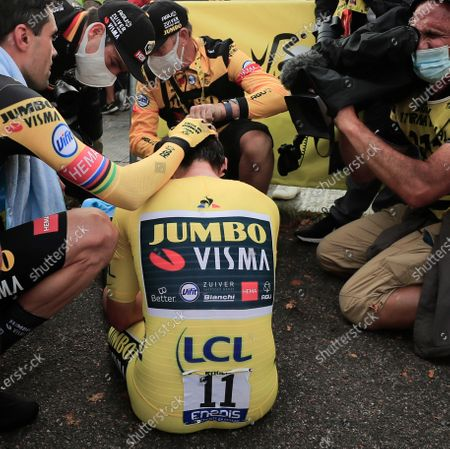 Slovenia's Primoz Roglic is comforted by teammates Tom Dumoulin of The Netherlands, left, and Belgium's Wout van Aert, second left, after losing the overall leader's yellow jersey in stage 20 of the Tour de France cycling race, an individual time trial over 36.2 kilometers (22.5 miles), from Lure to La Planche des Belles Filles, France