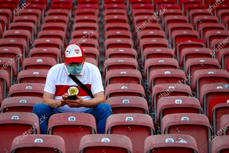 Stuttgart fan waits for the start of the German Bundesliga soccer match between VfB Stuttgart and SC Freiburg, Germany, . 8500 spectators are allowed to watch the game in the stadium